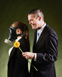 A smiling man holds out a yellow flower to a woman wearing a gas mask. Could represent allergies,asthma, pollution or even body odor!
