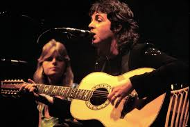 Paul McCartney singing with acoustic guitar